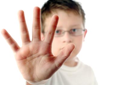 boy holding up hand